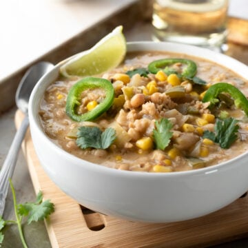 close up of white chili in a bowl topped with lime wedge and jalapeño