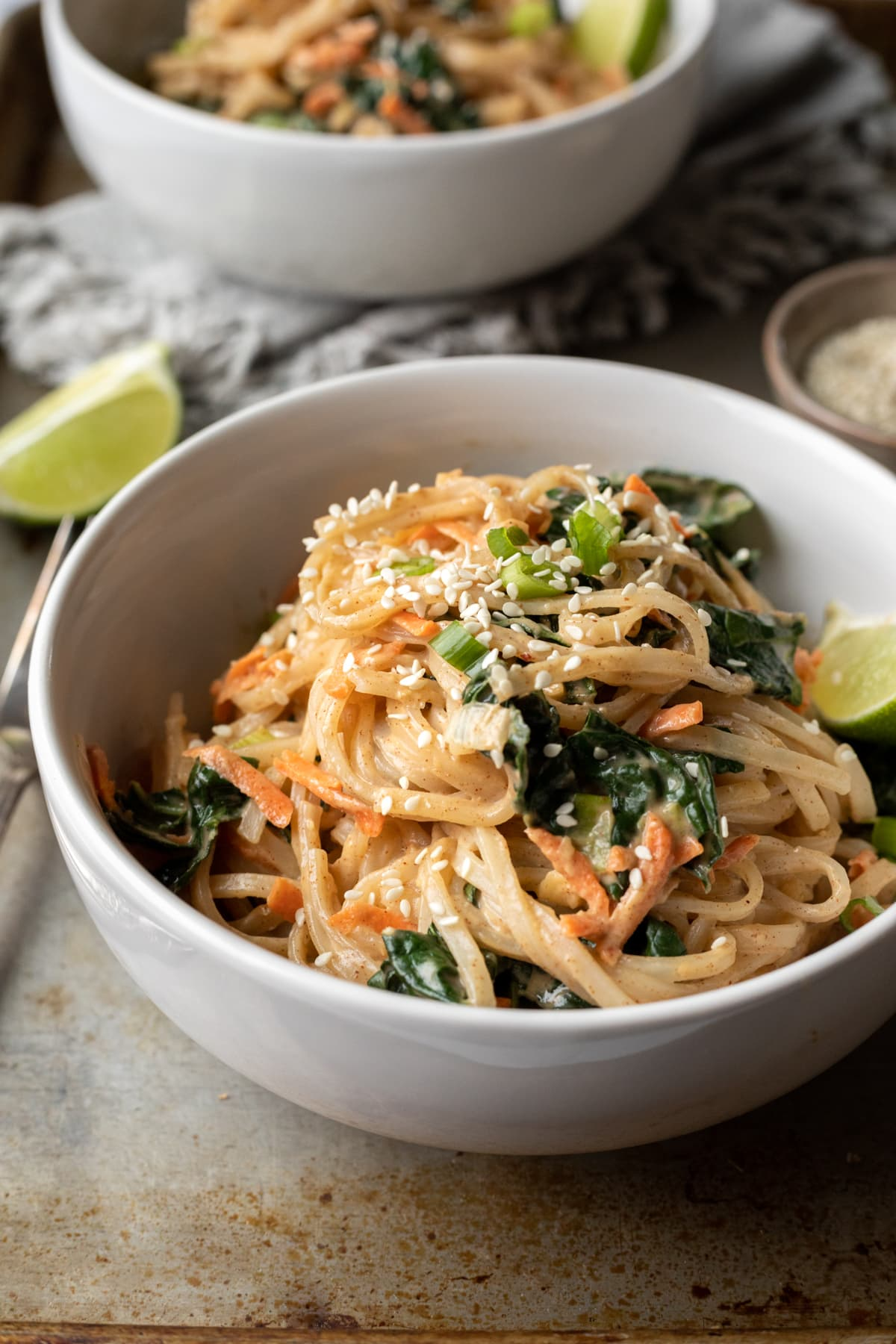 two bowls full of noodles with kale, carrot, and lime