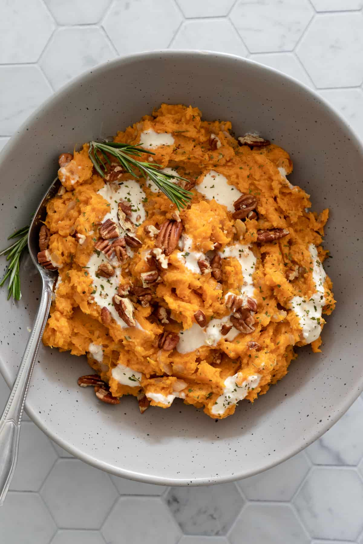 colorful sweet potato mash in a bowl swirled with yogurt
