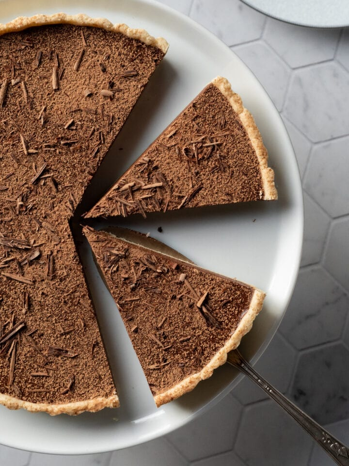 top view of chocolate tart on white plate with slices cut