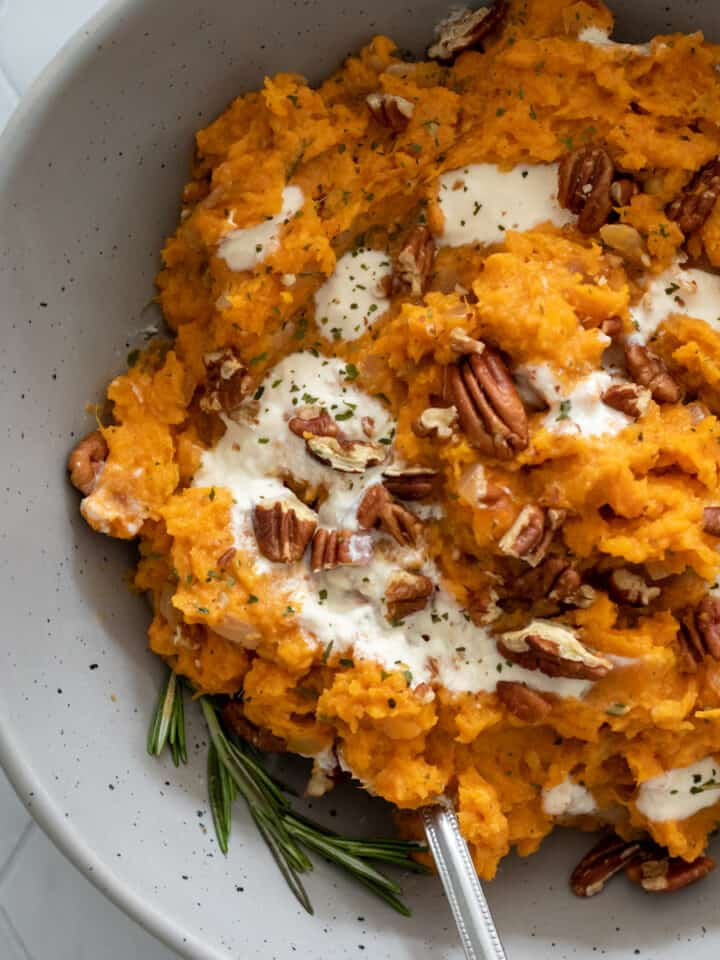 creamy sweet potato mash in a bowl with pecans and yogurt