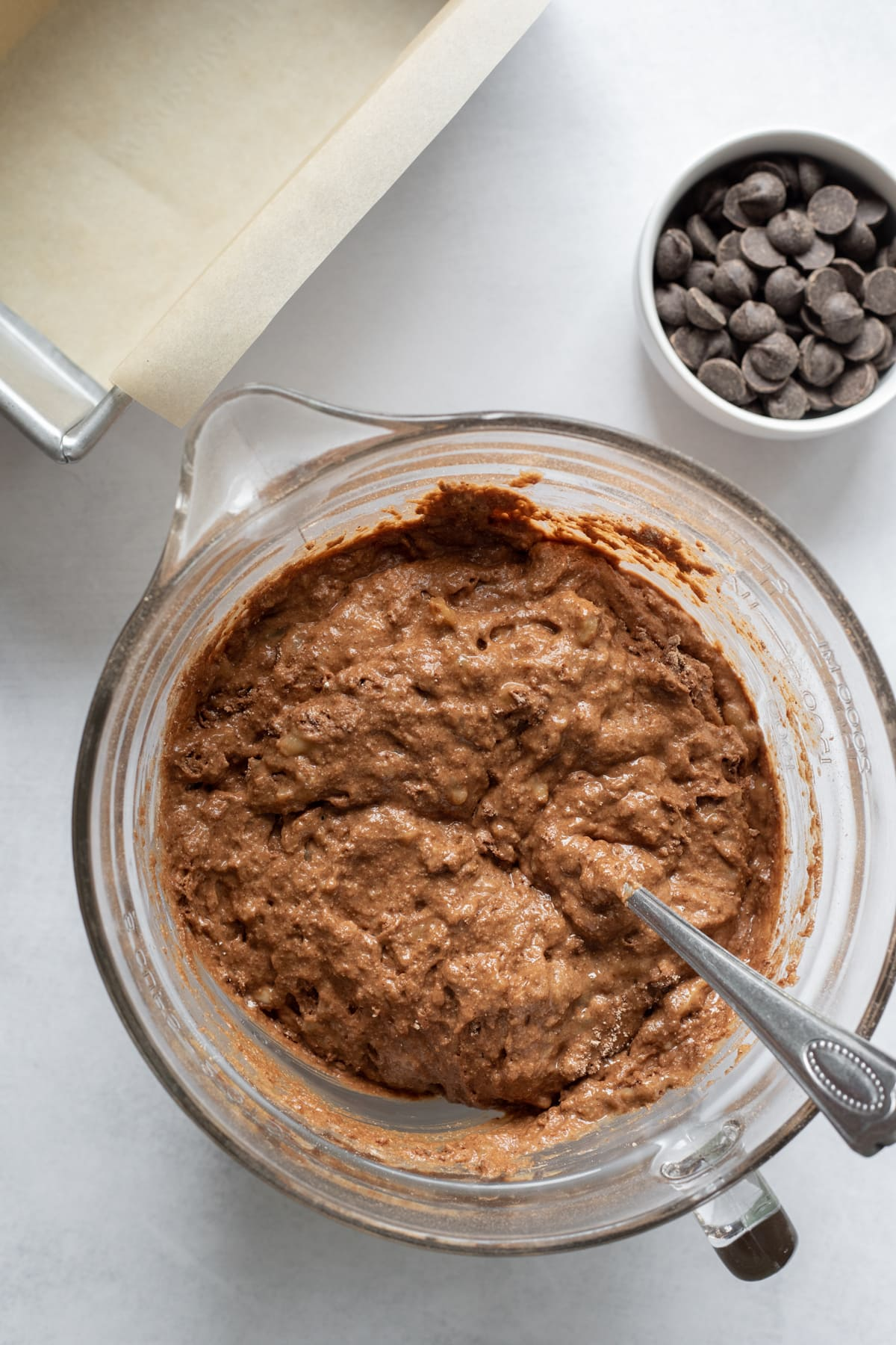 batter in a bowl with chocolate chips and parchment lined pan to the side