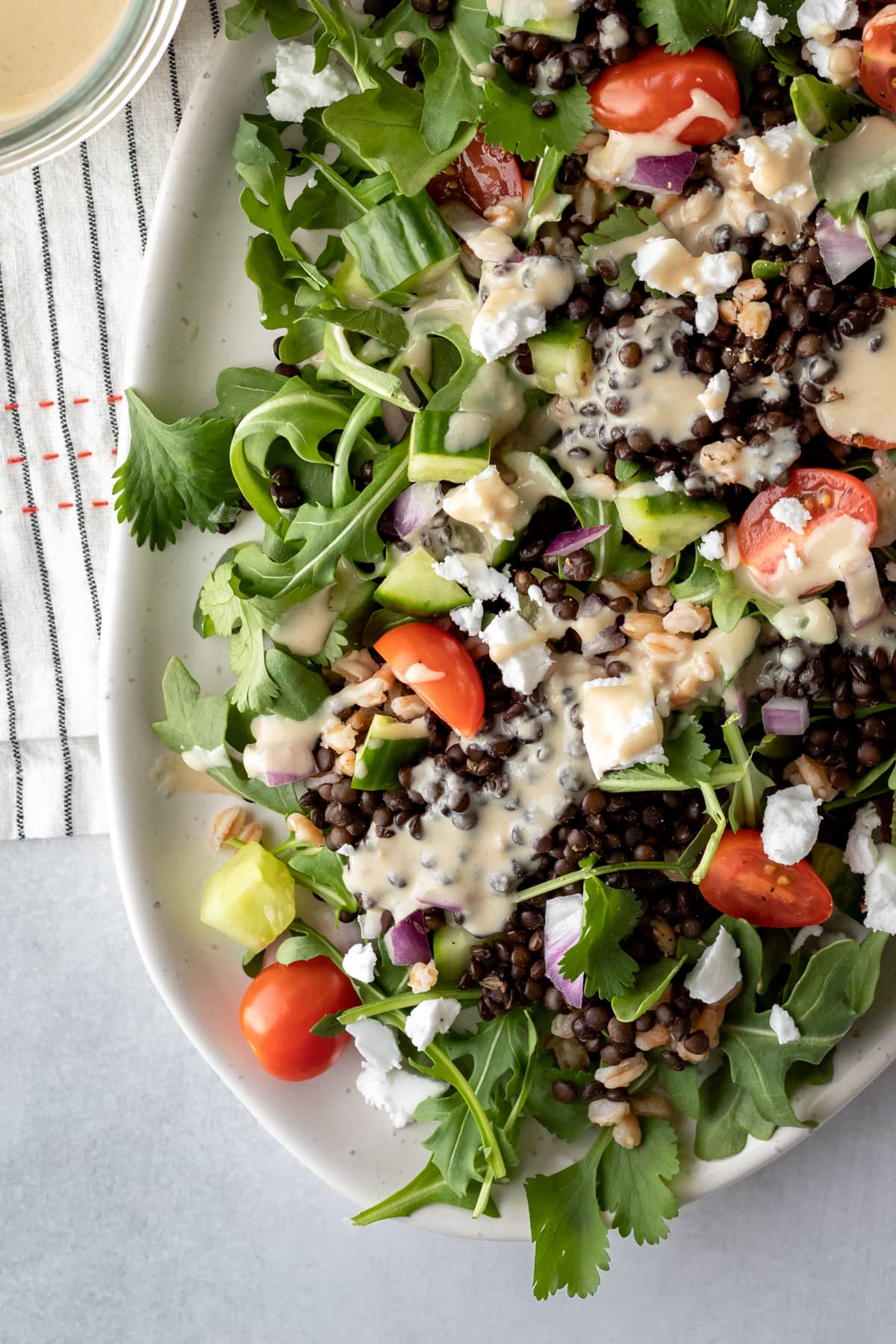 close up of salad topped with dressing and feta