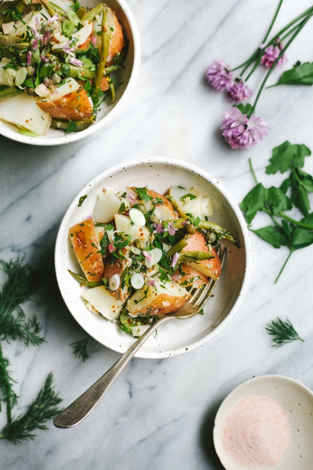 overhead view of colorful potato salad with fresh chopped herbs
