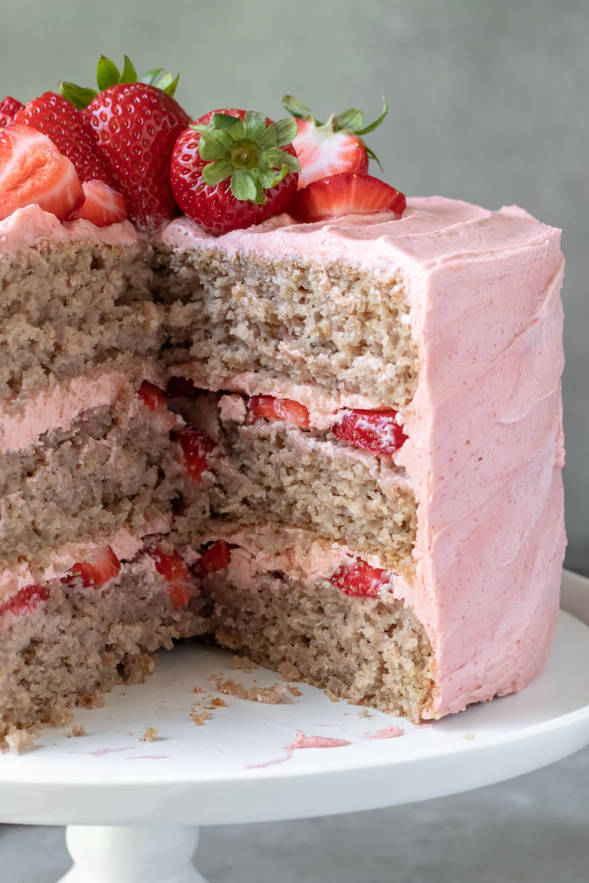close up of 3-tier cake with slices removed showing natural color of strawberry cake, no dye