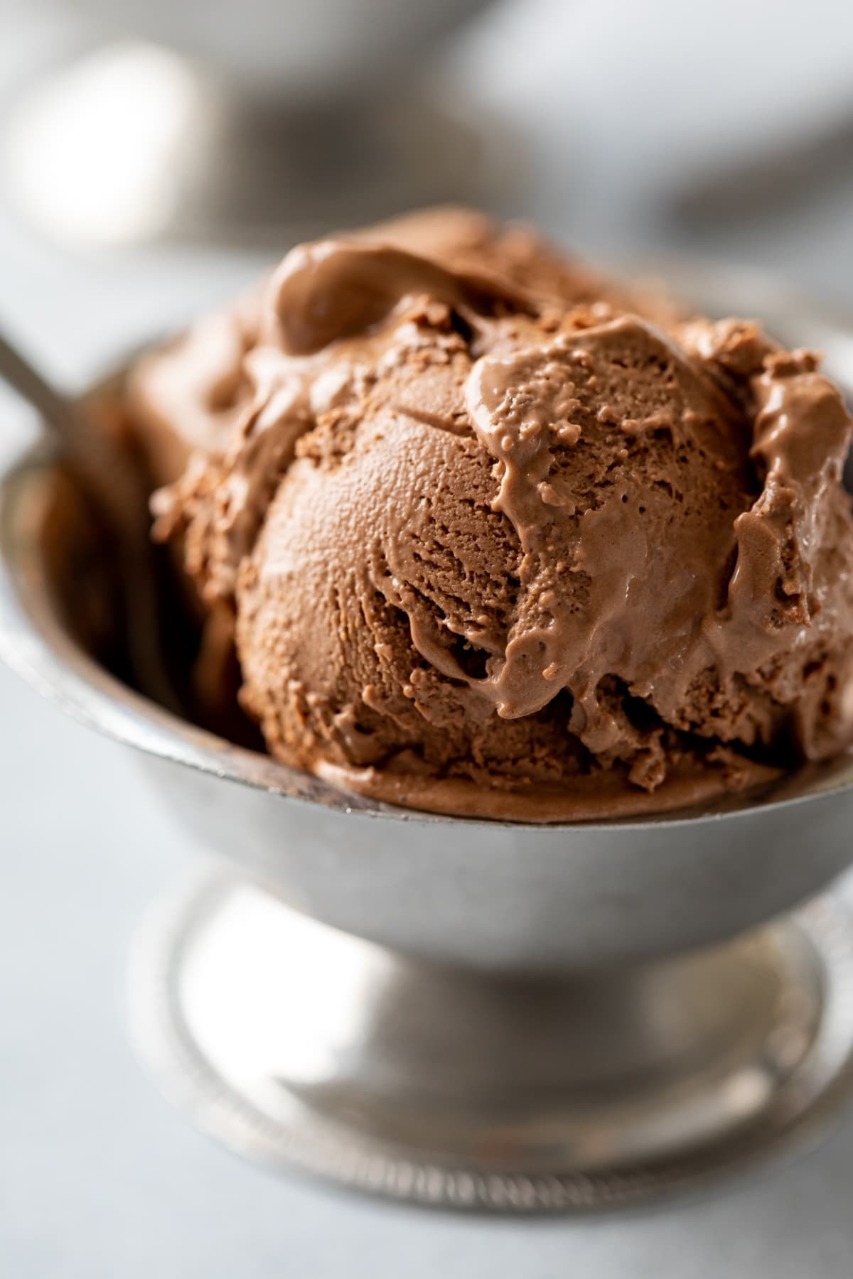 close up of texture of chocolate dairy-free ice cream, 2 scoops in a bowl