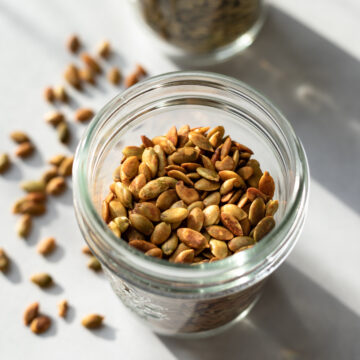 close up showing color and texture of roasted pumpkin seeds in a jar
