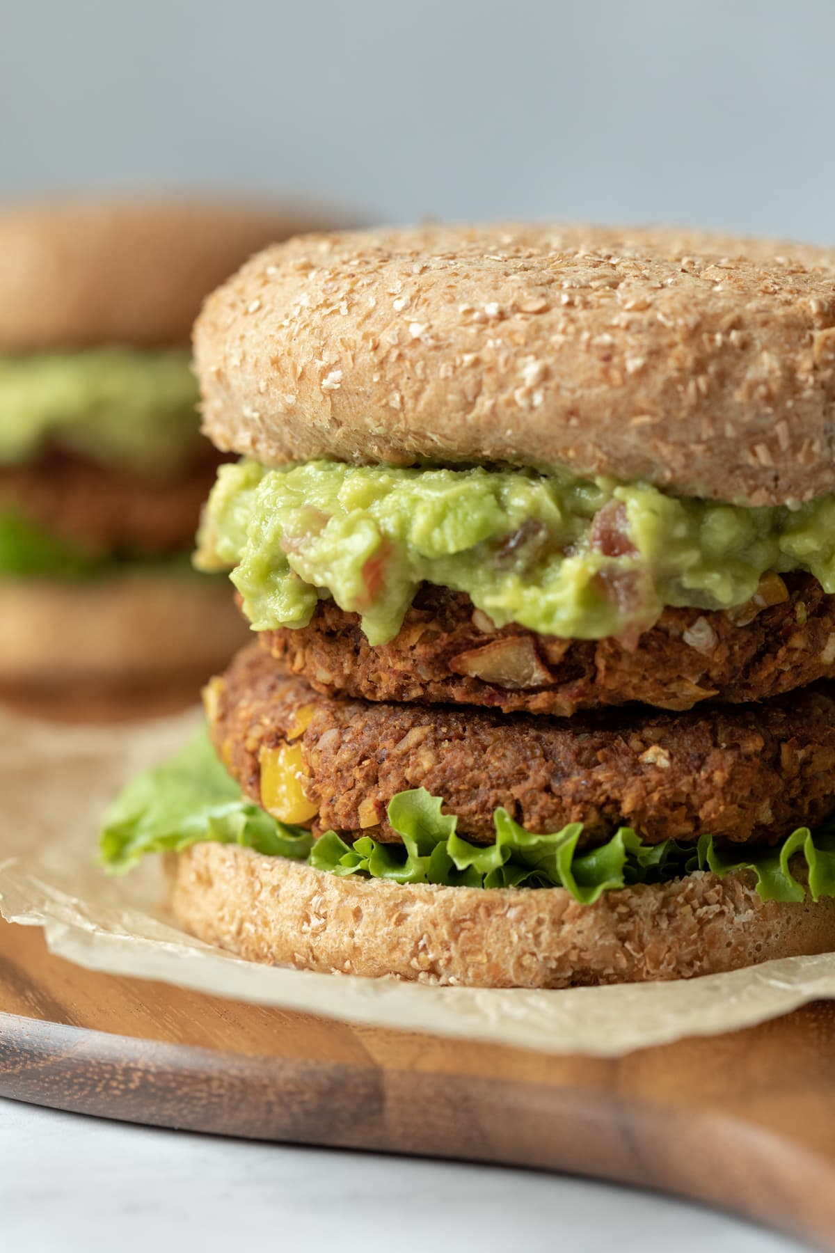 two vegan chickpea patties stacked on a bun and topped with guacamole