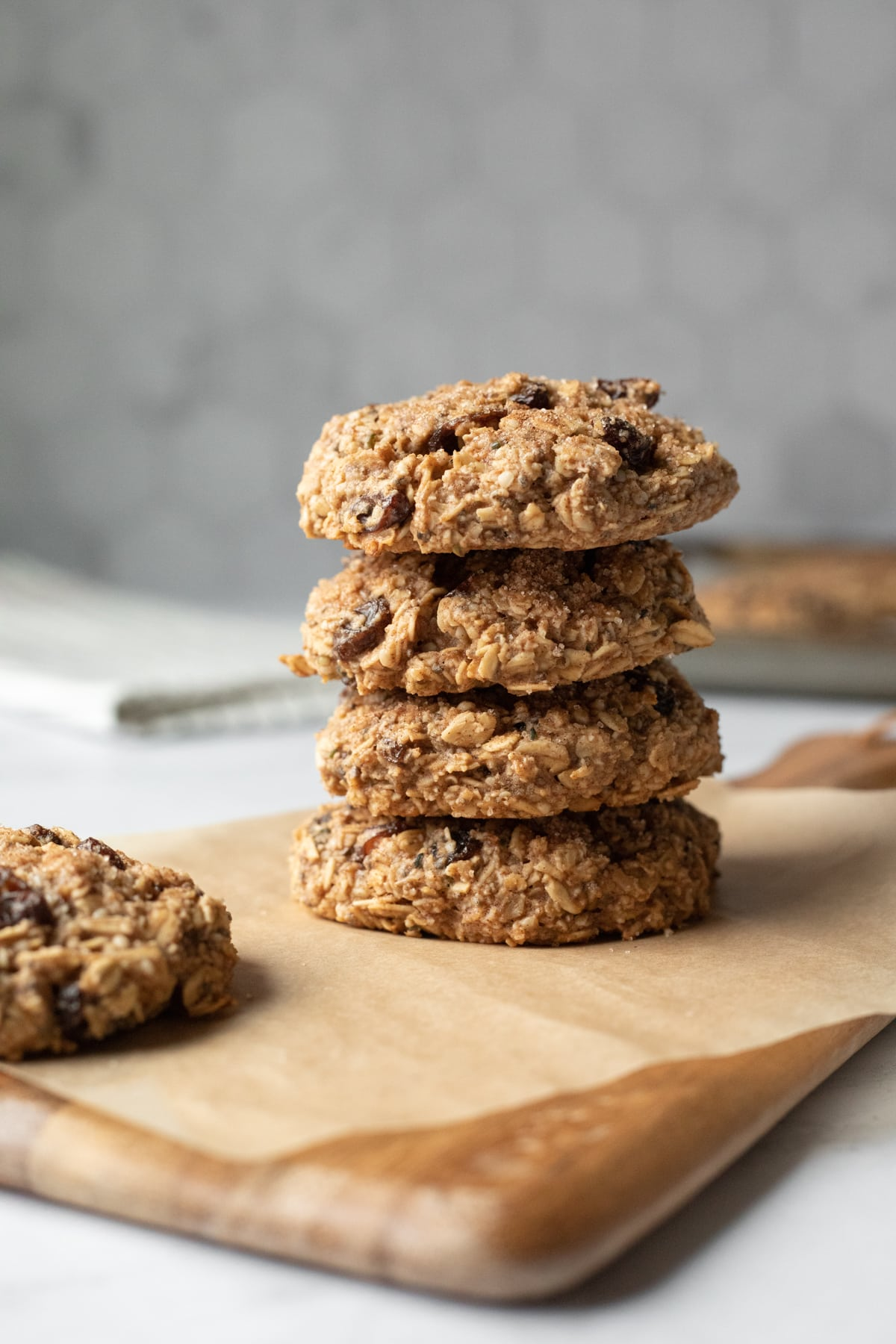 stack of 4 plump and chunky cookies agains a gray tile background.