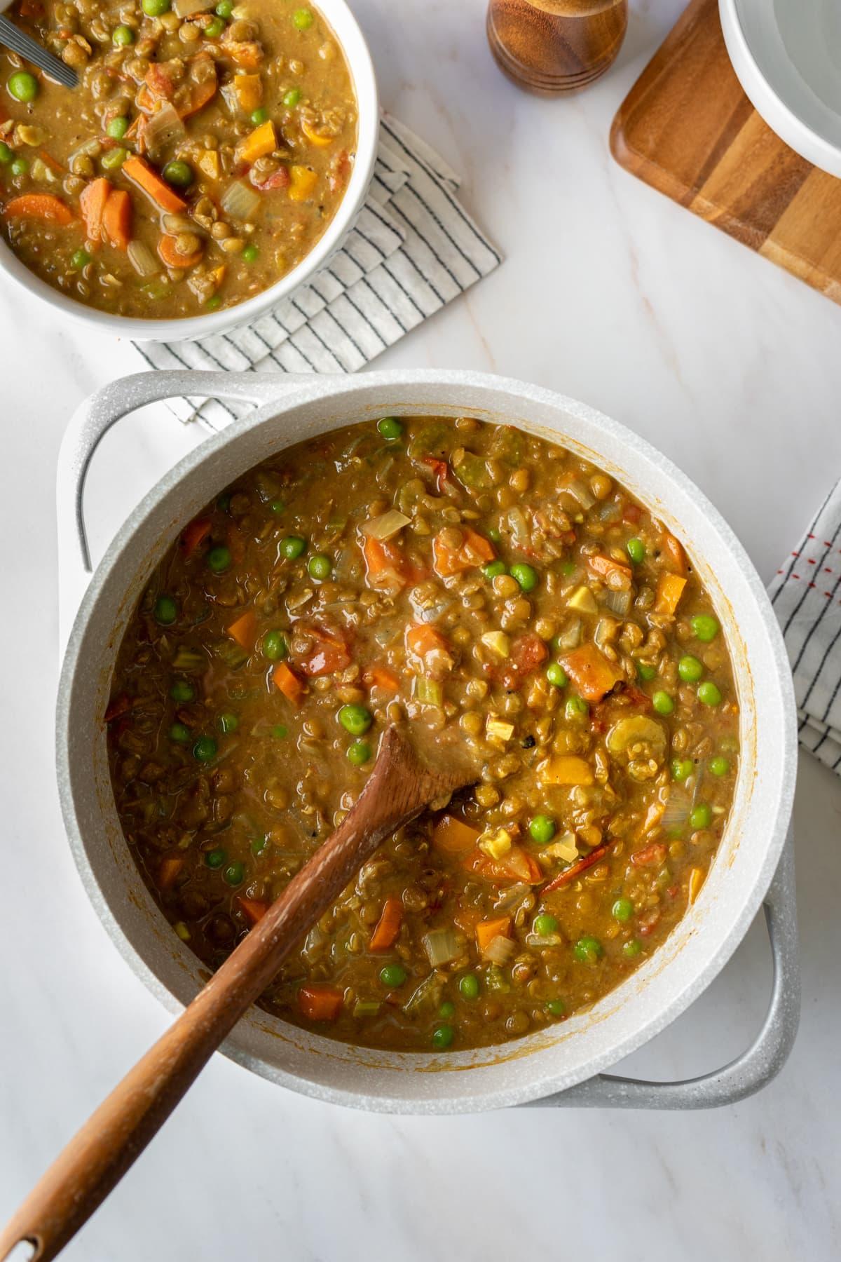 serving lentil soup from a large pot