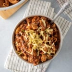 thick chili mac in a white bowl topped with shredded vegan cheese