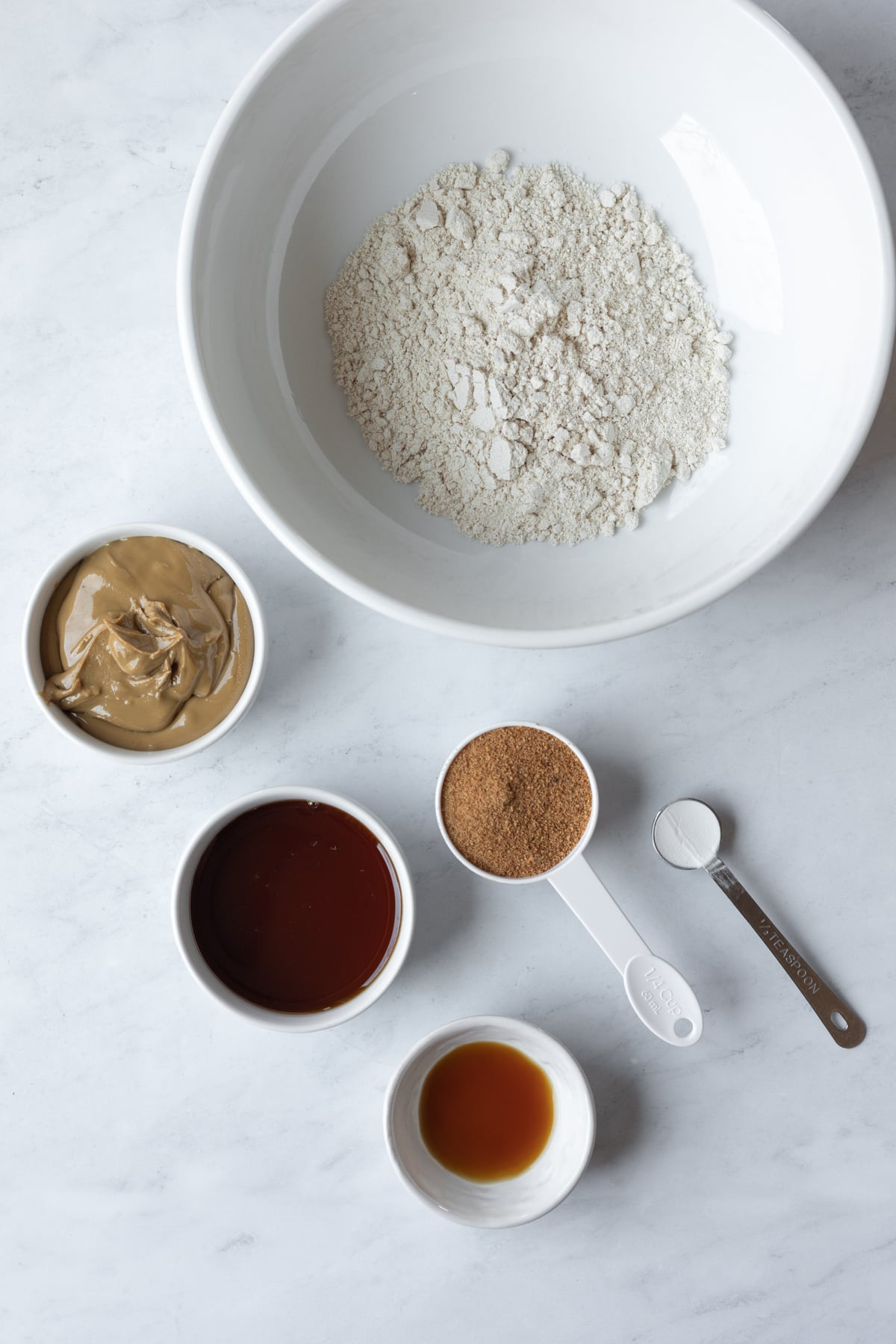 ingredients laid out on marble counter - oat flour, sunbutter, coconut sugar, maple syrup, vanilla