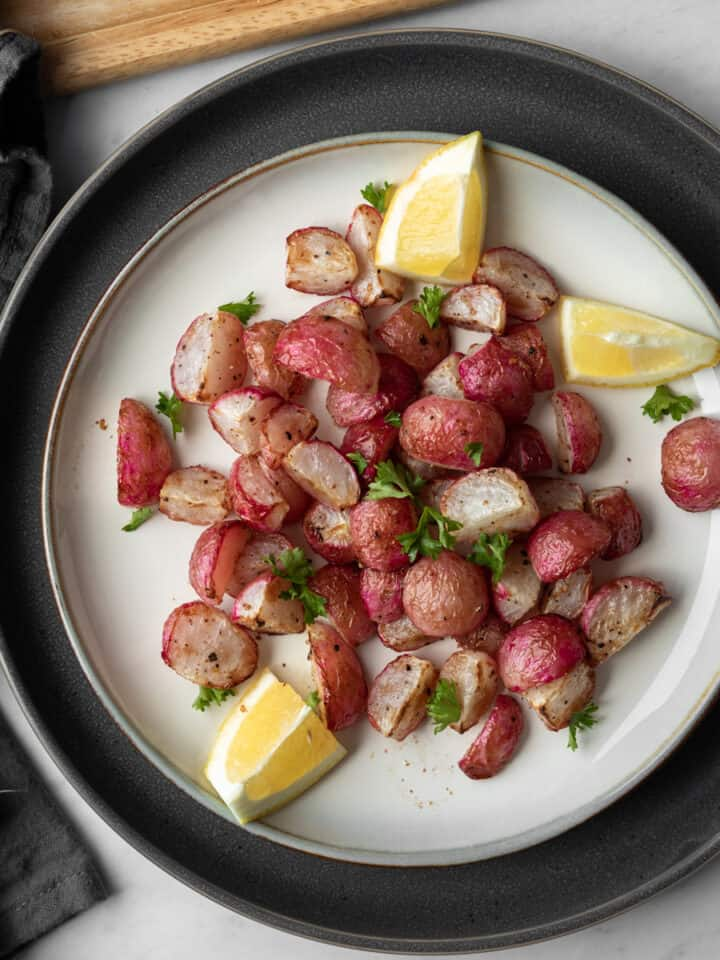 cooked radishes on a white plate garnished with lemon and parsley