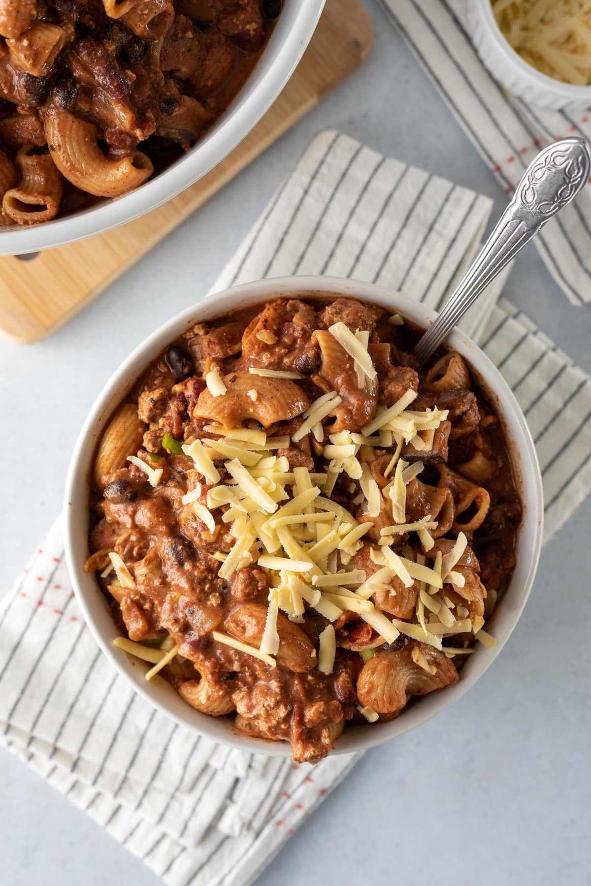 serving of chunky chili mac topped with shredded cheese