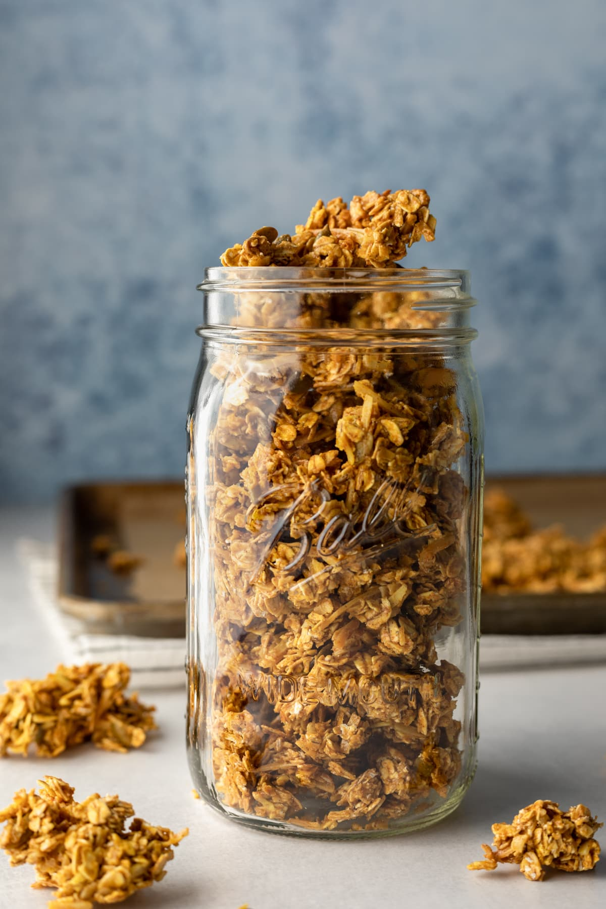 golden colored clusters of granola in a large glass jar