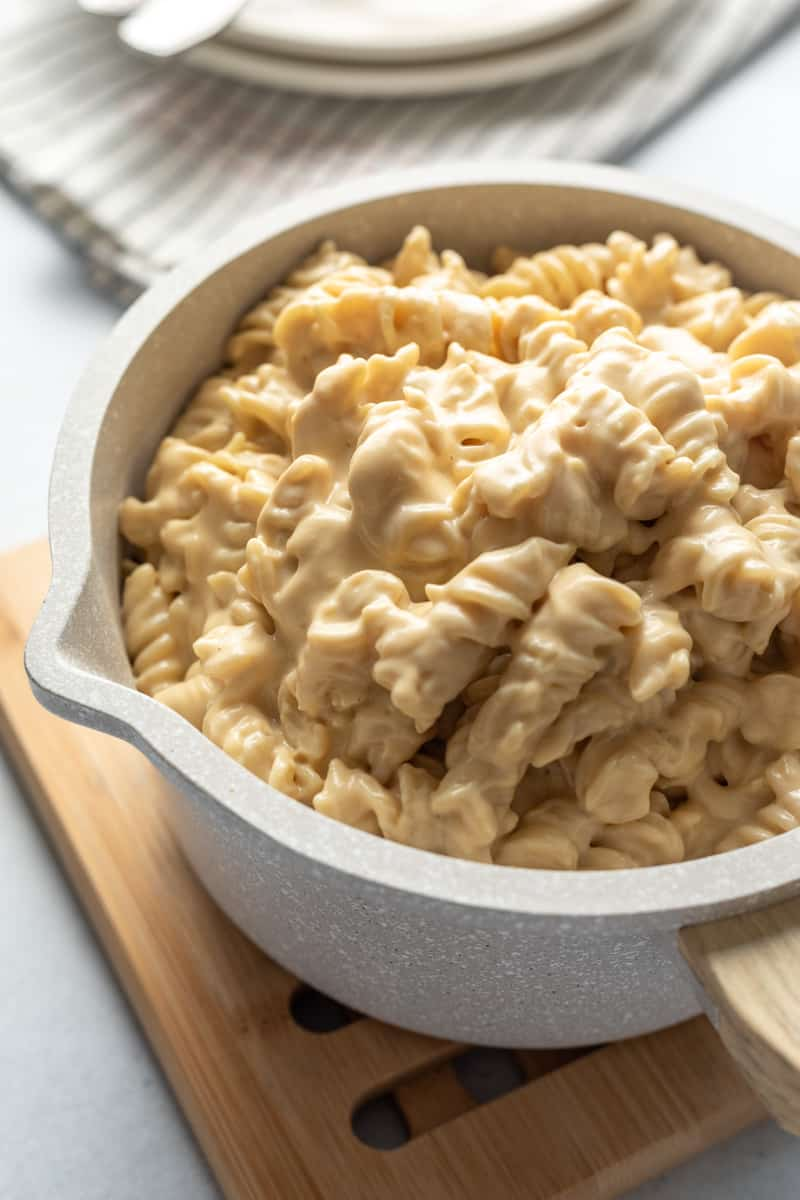 backlit photo of super creamy looking mac and cheese in a pot.