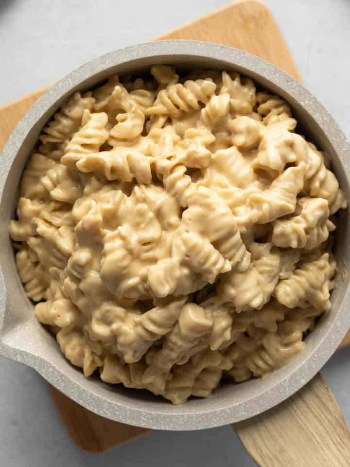 creamy macaroni and cheese in a small pot sitting on a wood trivet