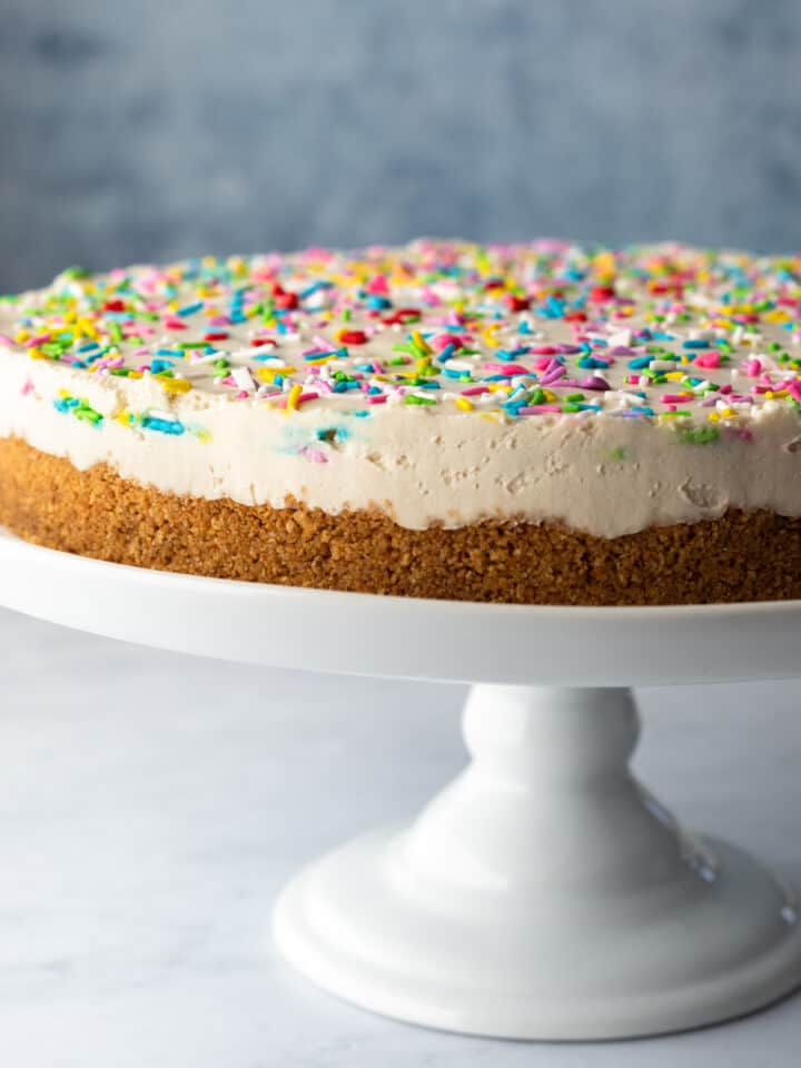 whole cheesecake resting on a white cake stand