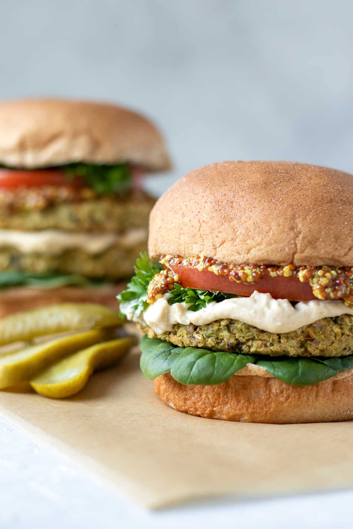 Tabbouleh-Inspired Bean Burgers topped with tomato, parsley, spinach, mustard and hummus.