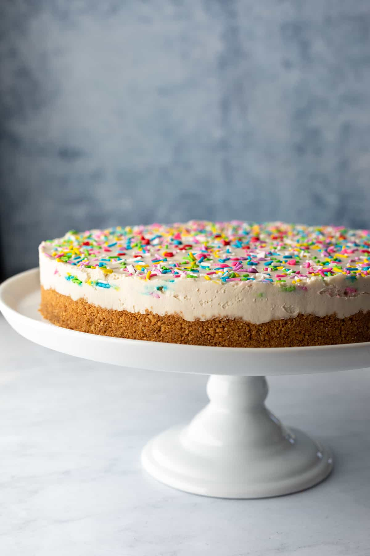 whole cheesecake topped with colorful vegan sprinkles on a white cake stand against a blue background