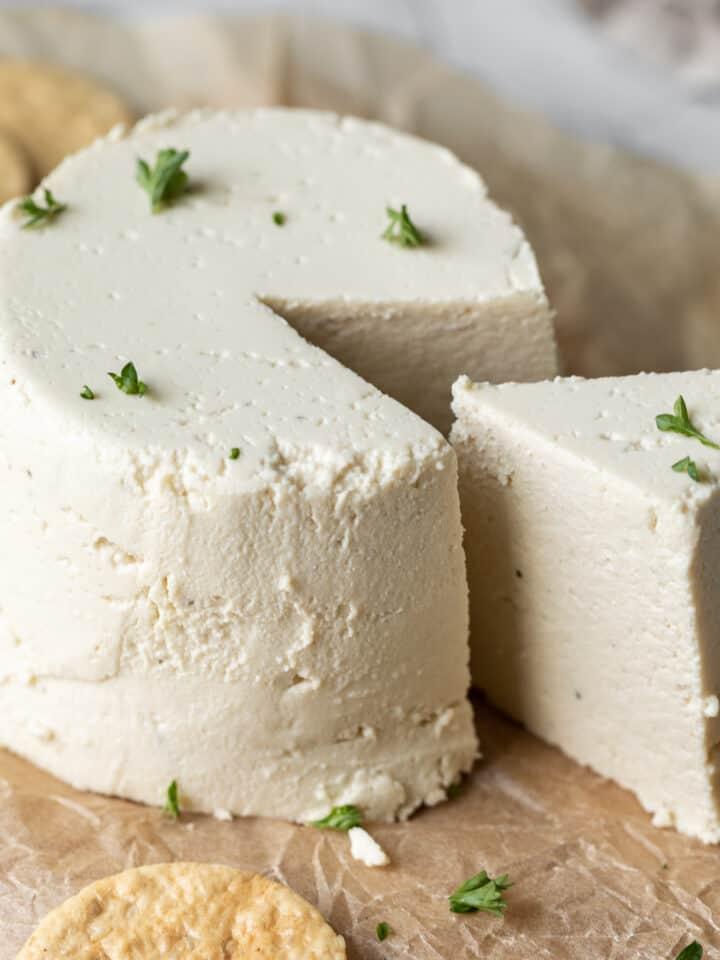 wedge slice cut from wheel of vegan cheese