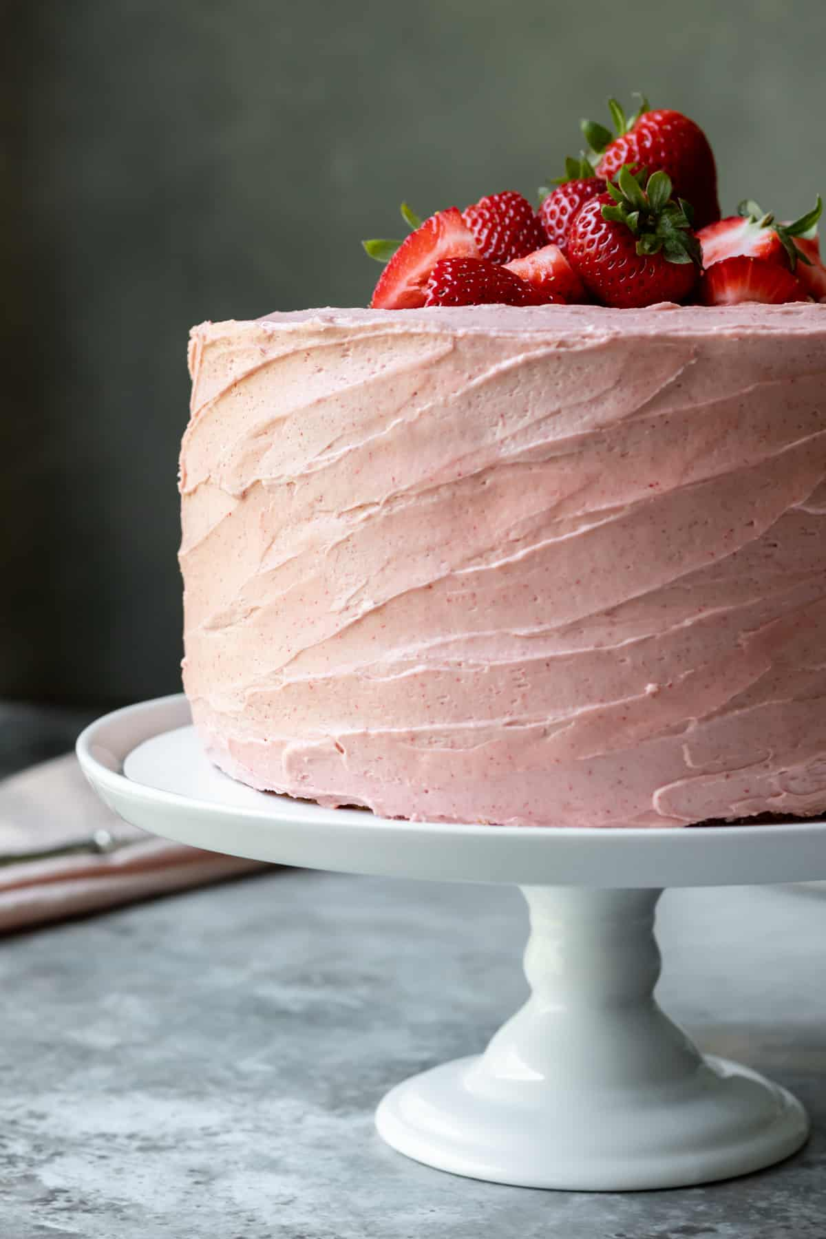 side view of fully frosted cake on white cake stand with strawberries on top.