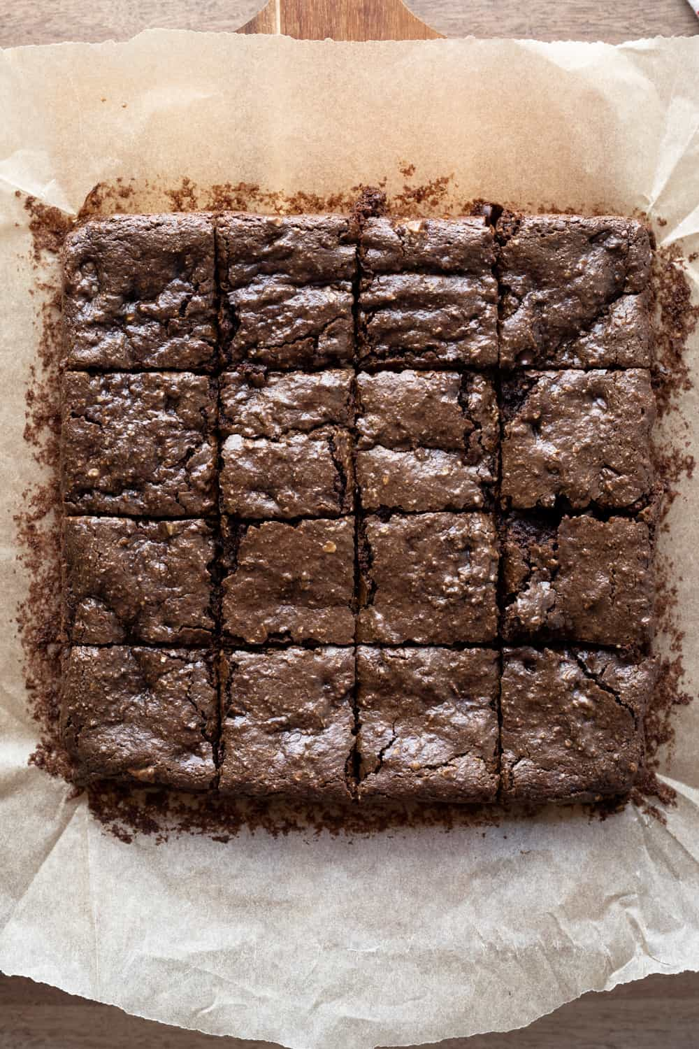 Overhead shot of brownies with shiny, crinkly tops cut into 16 squares.