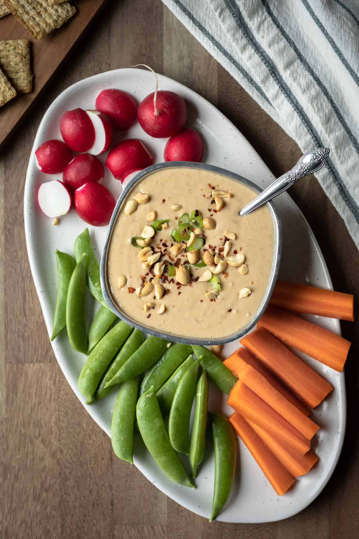 small bowl of peanut dip on a platter surrounded by raw veggies.