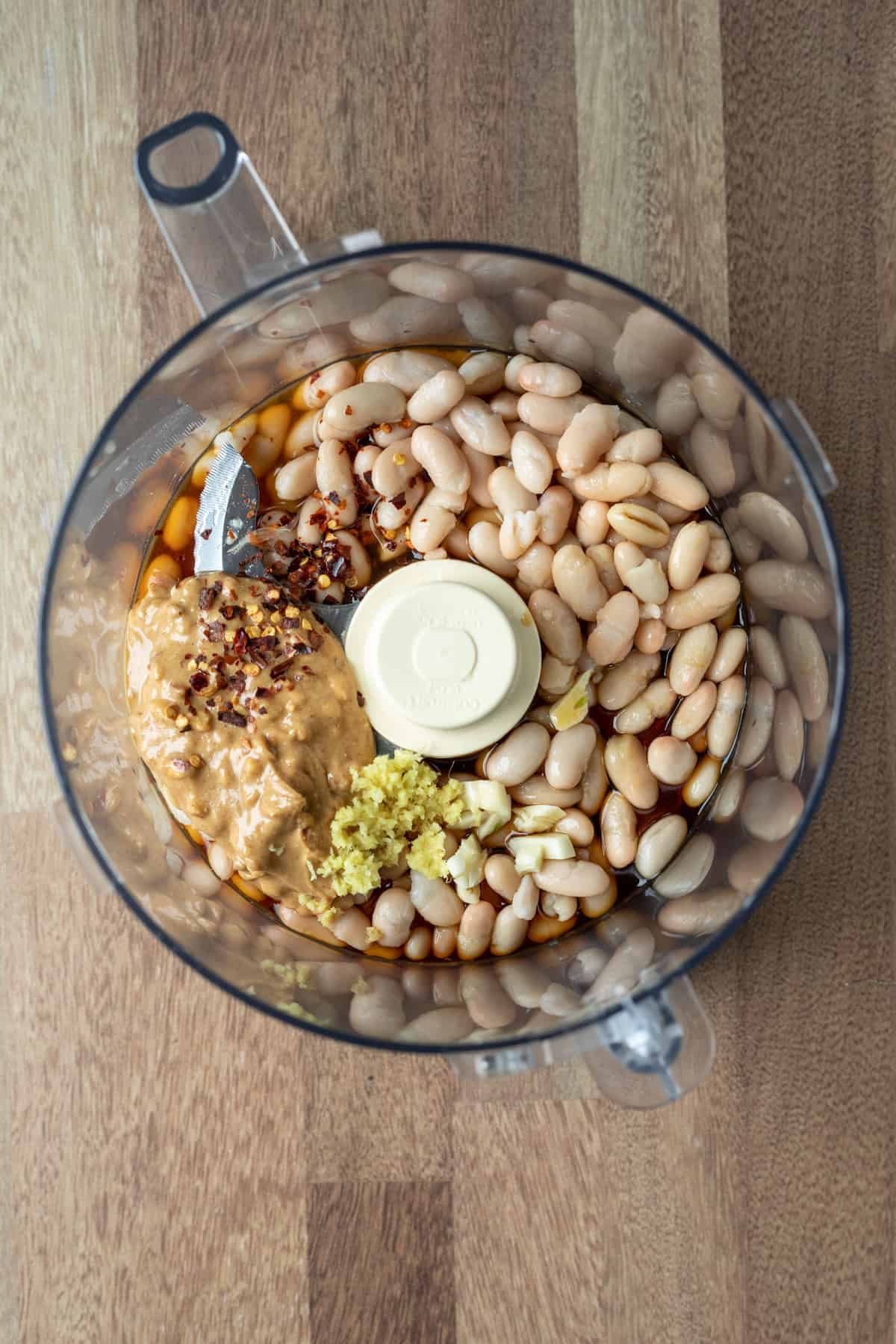 ingredients inside the bowl of a food processor before blending.