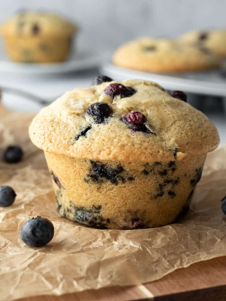 blueberry muffin on a board with more muffins in background.