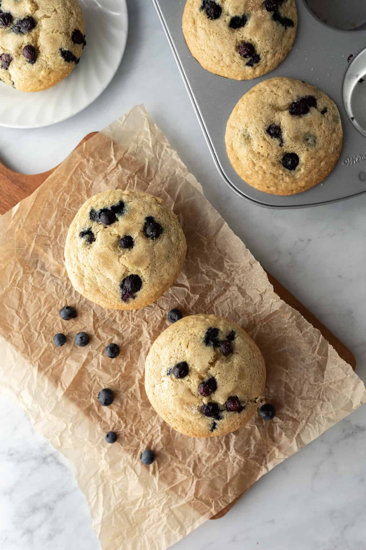 overhead shot of two blueberry muffins on a board with jumbo muffin pan nearby.