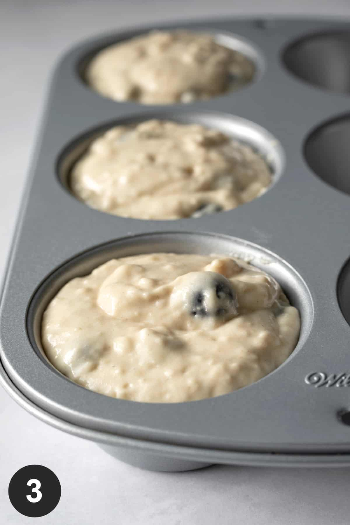 close up photo showing thick batter filling muffin cups almost to the top.