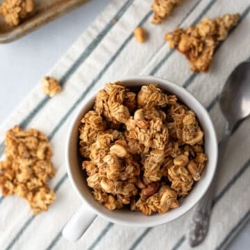 clusters of granola with peanuts in a mug and nearby.