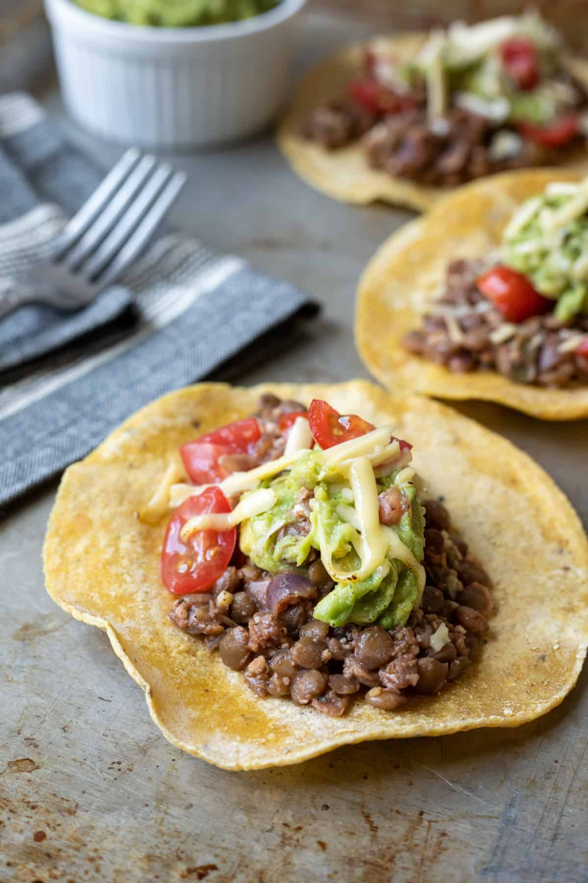 three tacos with lentils, guacamole, cheese, and tomatoes.