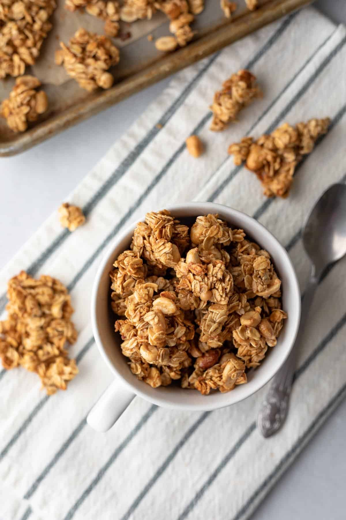 big clusters of golden granola in a mug.