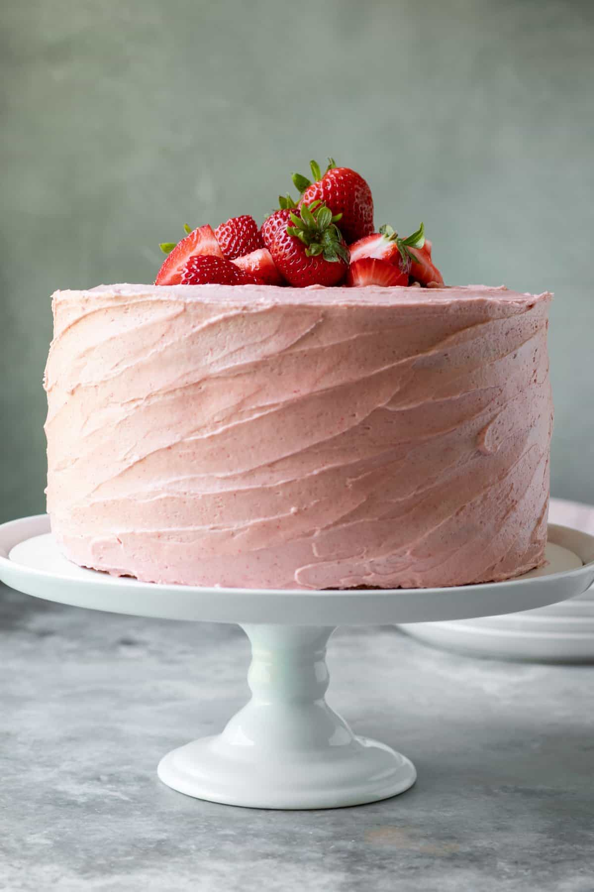3-layer frosted cake on a white cake stand.