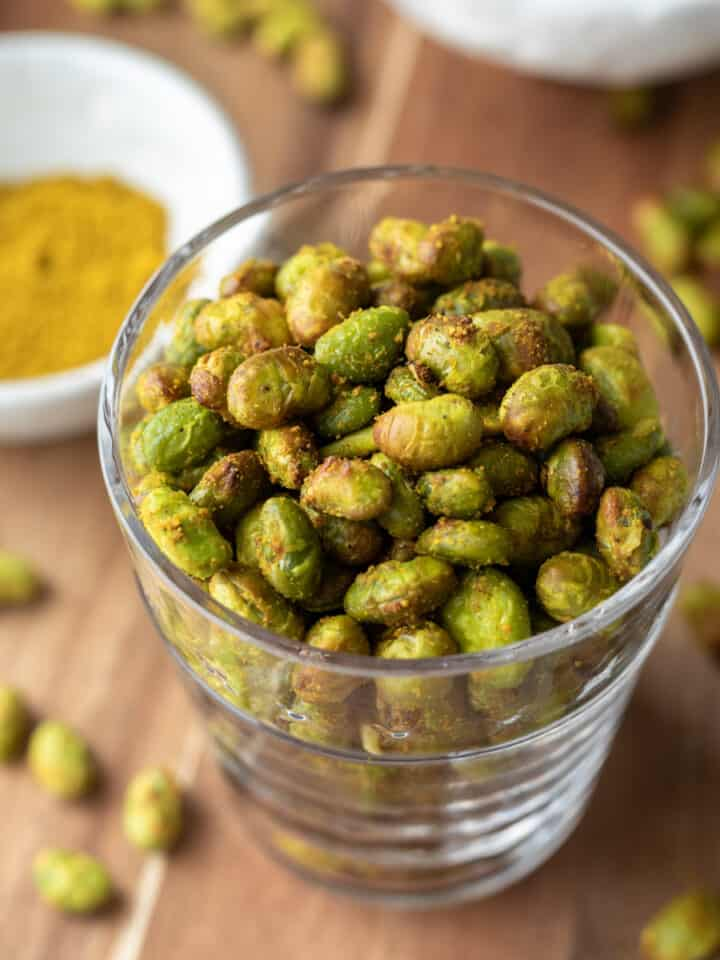 looking down at crispy roasted edamame in a glass.