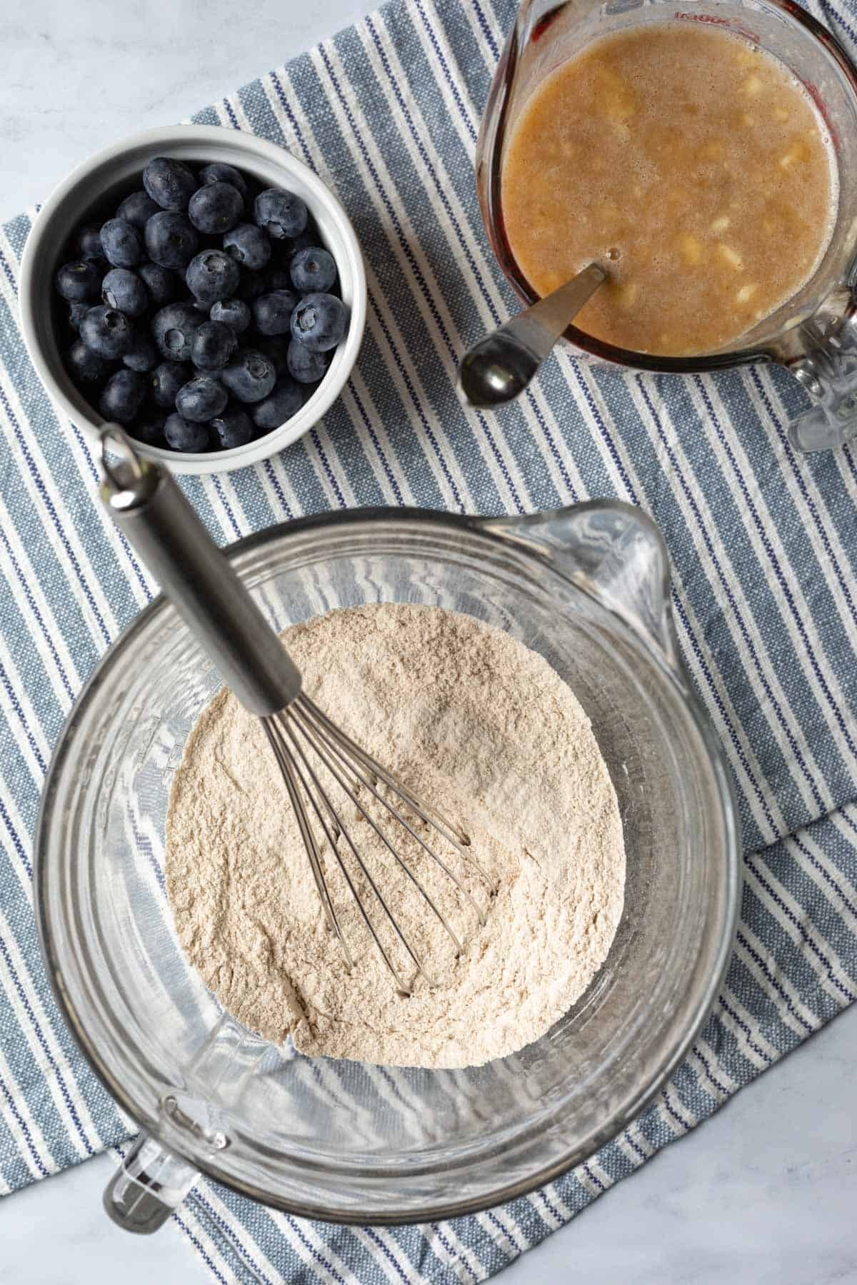 Three bowls with separate components of muffins: dry and wet ingredients and blueberries.
