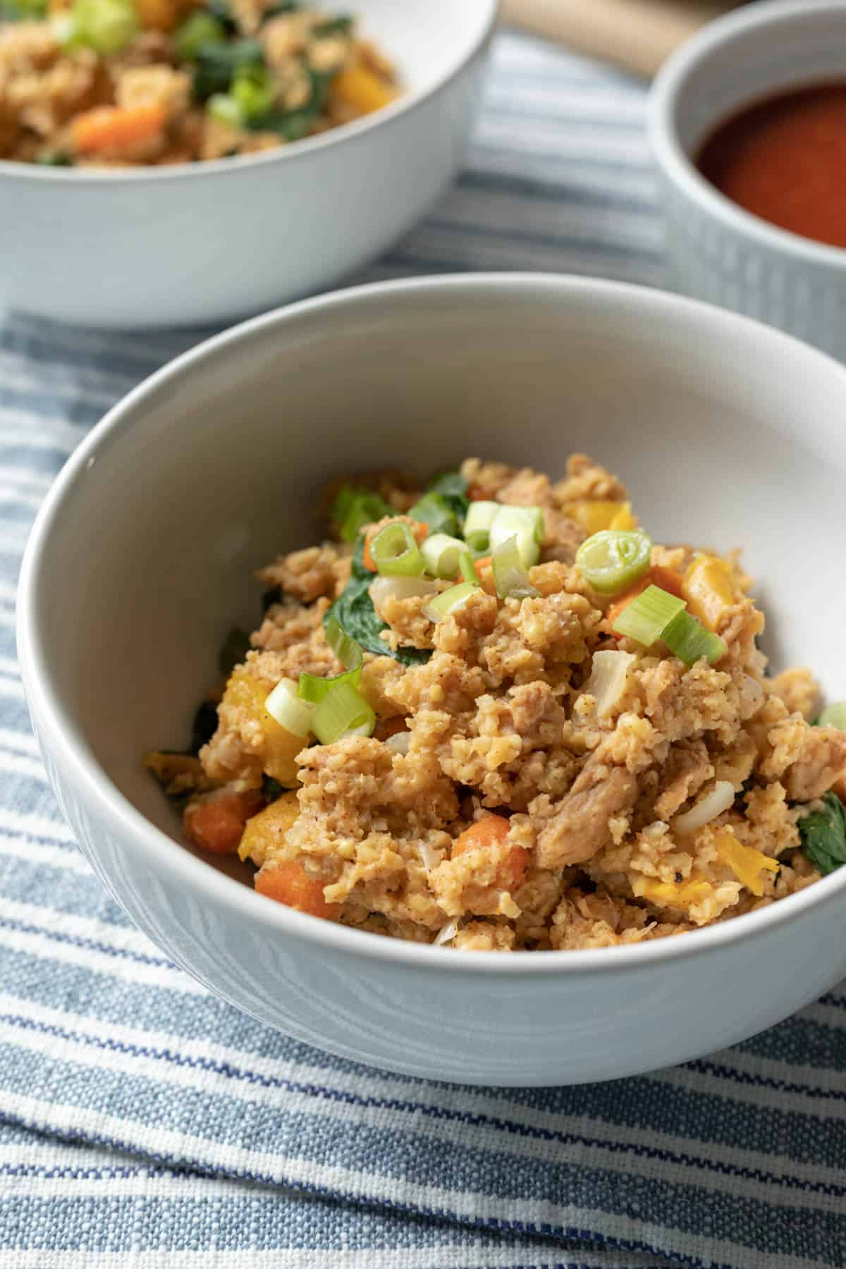 full meal of millet, vegetables, and soy curls in a bowl topped with green onion.