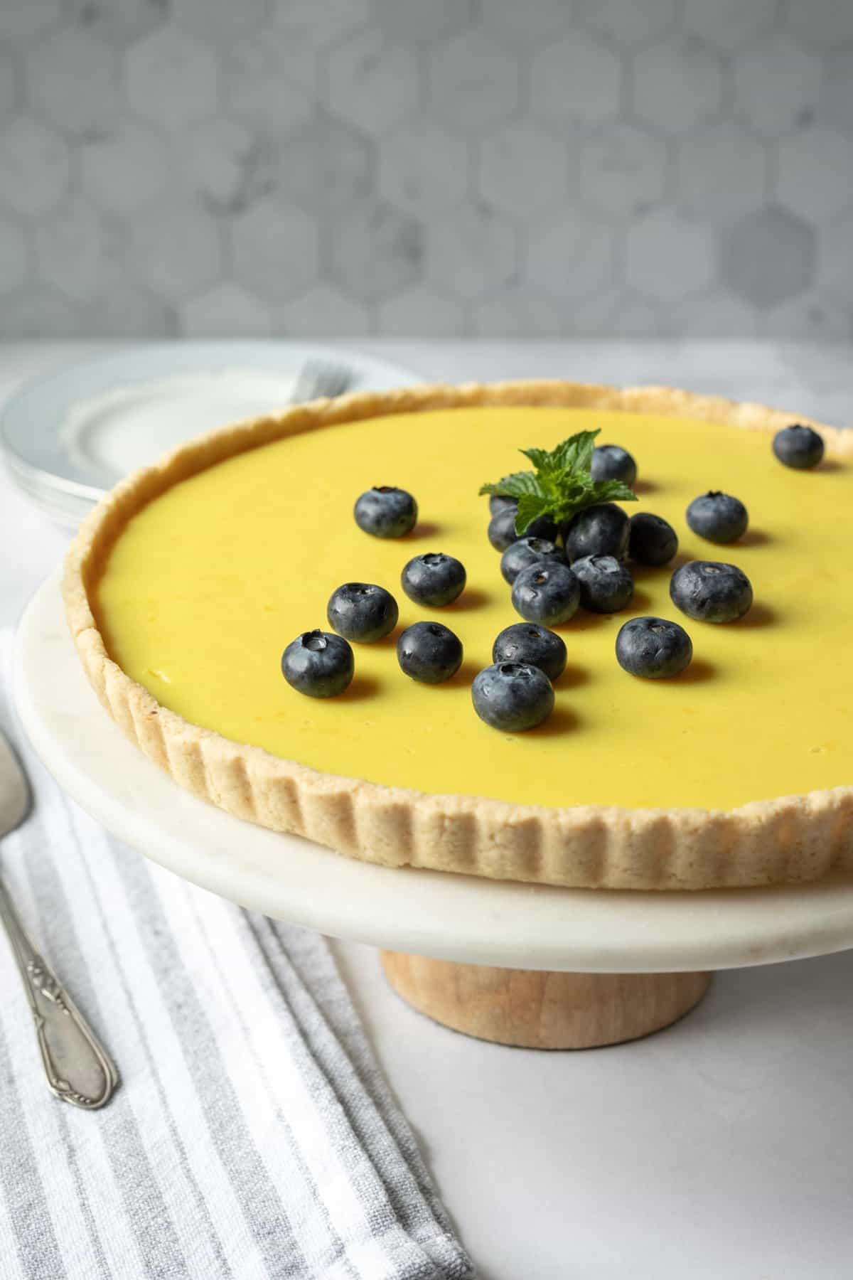 light lemon tart with almond flour crust on a cake stand.