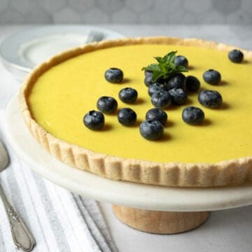 side view of lemon tart on a cake stand against gray tile background.