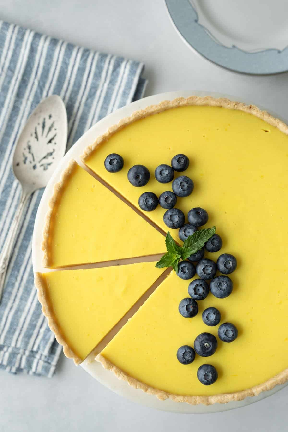 overhead of lemon tart decorated with blueberries on a white cake stand.