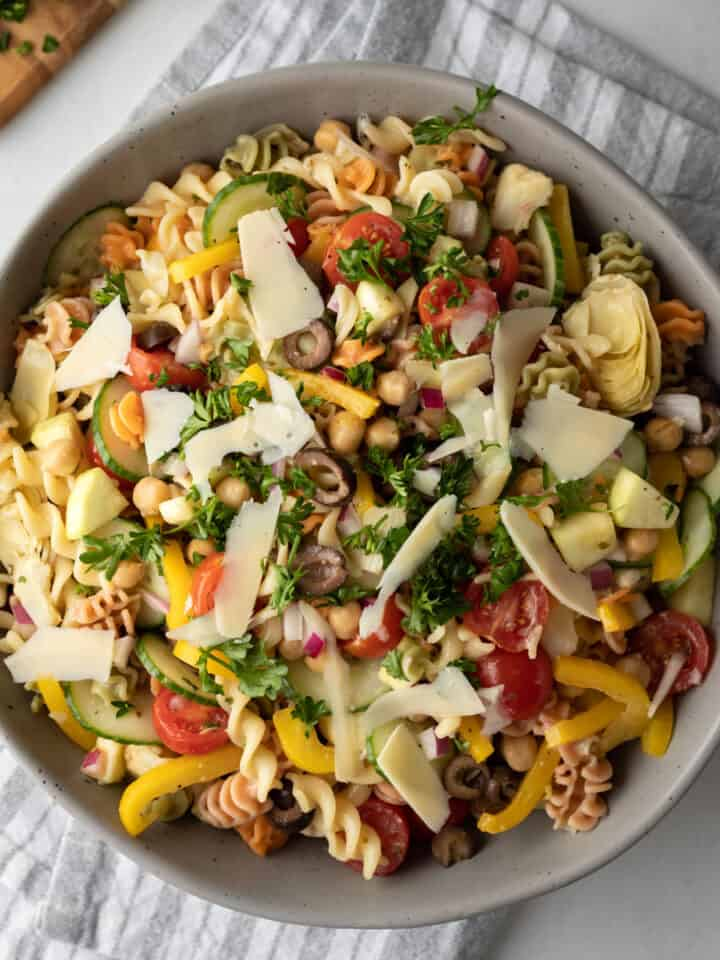 close up overhead view of assembled pasta salad topped with chopped fresh parsley.