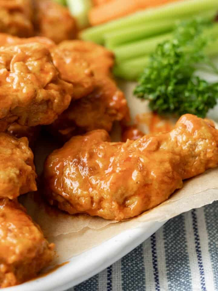 buffalo seitan wings on a serving platter with celery in background.