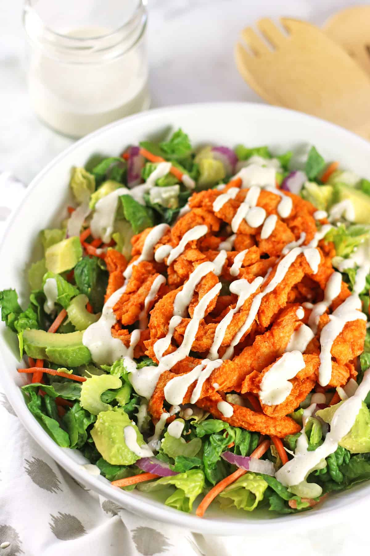 bright photo of a green salad topped with buffalo strips and avocado.