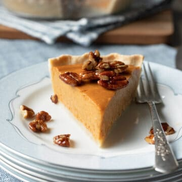 a slice of pie on a plate topped with candied pecans.