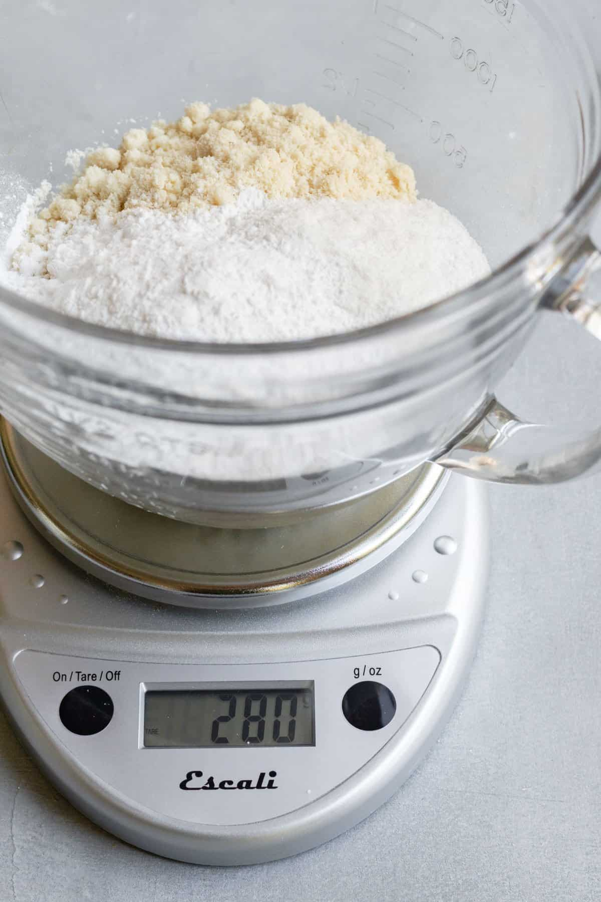 using a small kitchen scale to weigh flours.