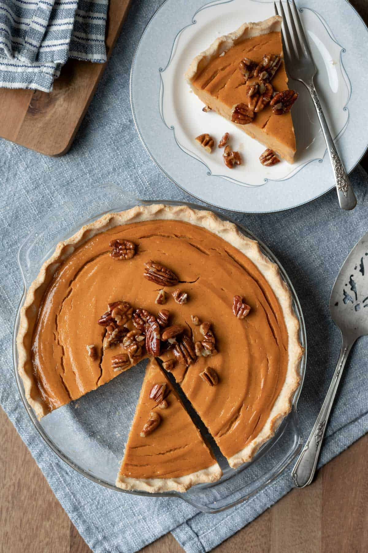 overhead of whole pie topped with candied pecans and one slice on a plate.