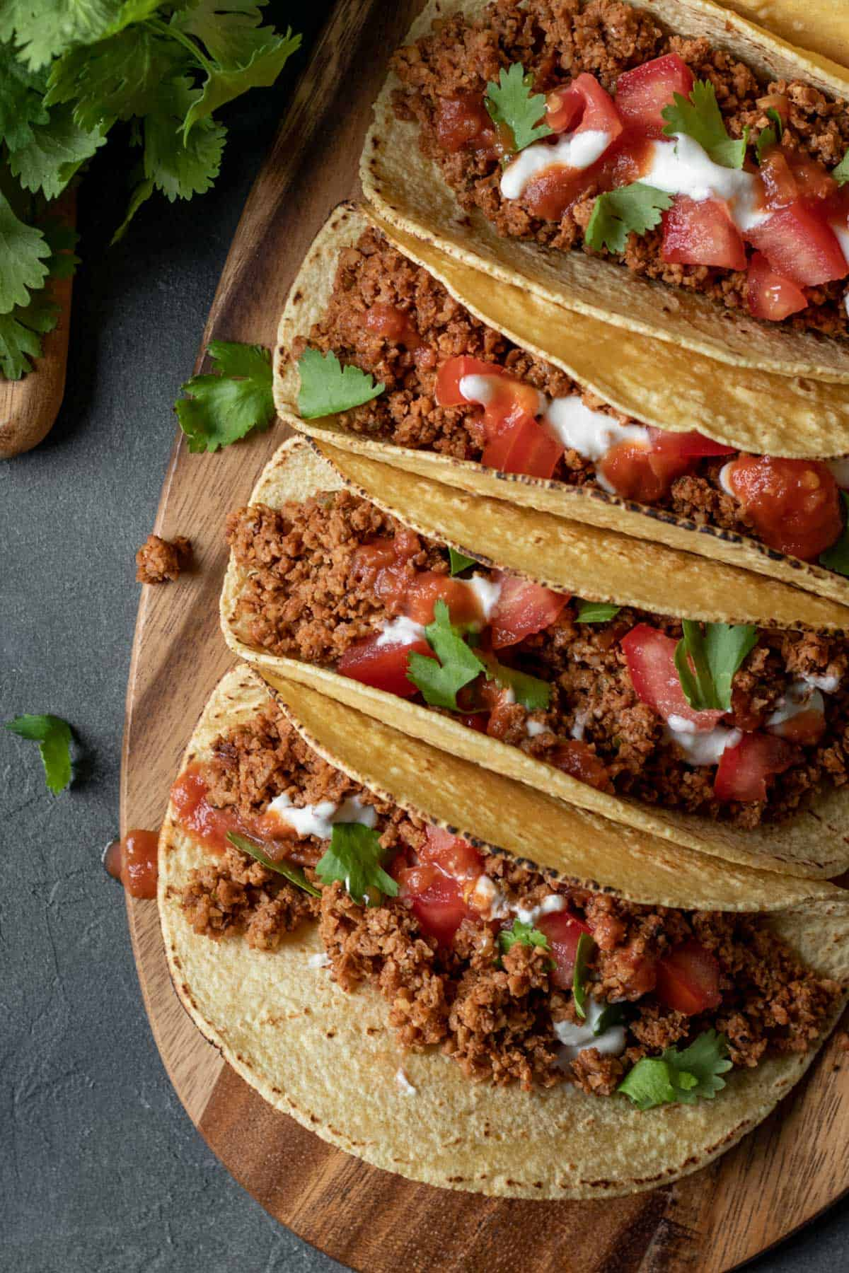soy curl tacos lined up on a wood board.
