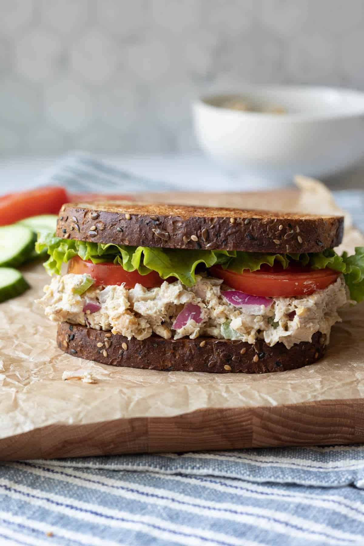 """a sandwich with whole-grain bread, creamy """"chicken"""" salad, lettuce and tomato."""